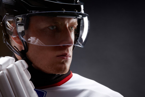 Face of sportsman in protective helmet over black background